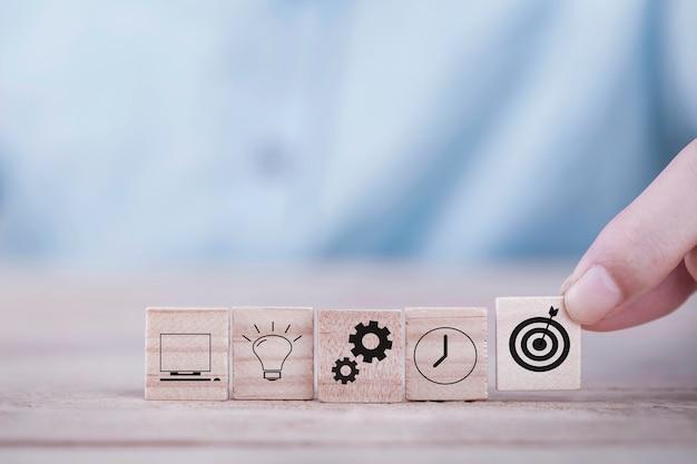 L'uomo d'affari sceglie un obiettivo delle icone dell'emoticon con il simbolo della freccia sul blocco di legno