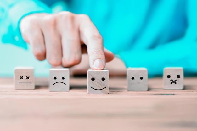 Uomo d'affari sceglie una faccia di icone emoticon felice sul blocco di legno.