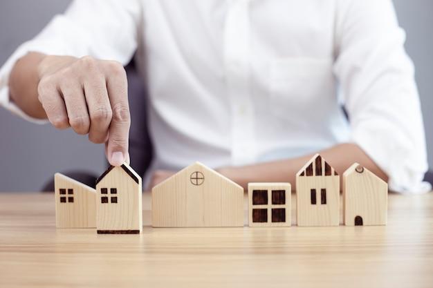 Uomo d'affari che sceglie la pianificazione del modello di casa per acquistare il concetto di prestito immobiliare