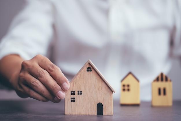 Uomo d'affari che sceglie il modello di casa e sta pianificando di acquistare proprietà