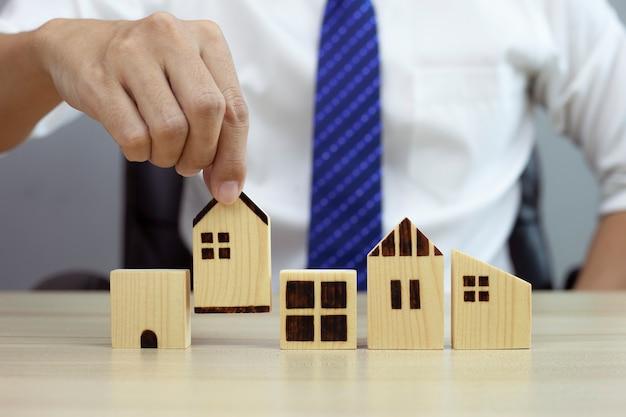 Uomo d'affari che sceglie una casa in legno e pianifica di acquistare un concetto di prestito immobiliare