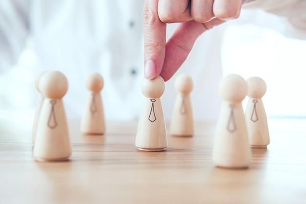 Imprenditore scegliendo persone in legno icona sulla scrivania in ufficio.