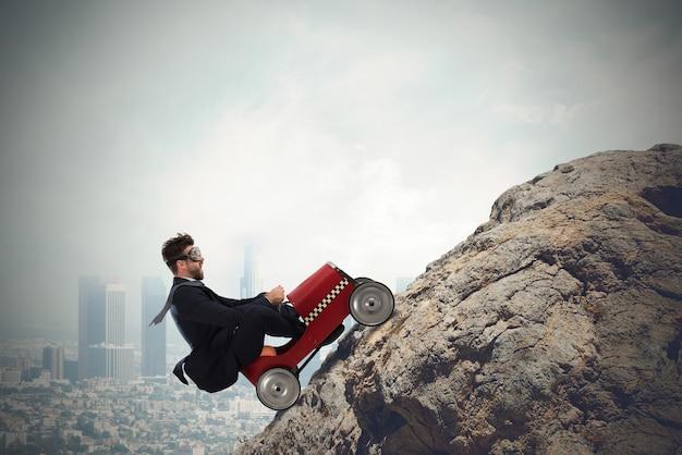 Uomo d'affari scalare una montagna con una piccola automobile. concetto di carriera difficile