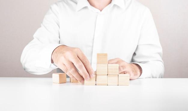 L'uomo d'affari scala la scala della carriera. concetto di affari dai cubi.