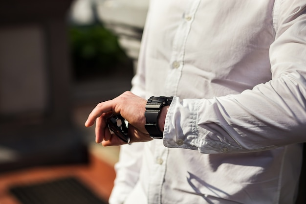 Vestiti dell'orologio dell'uomo d'affari, uomo d'affari che controlla tempo sul suo orologio. lancetta degli uomini con un orologio, orologio sulla mano di un uomo, le tasse dello sposo, preparazione al lavoro, chiusura dell'orologio, stile dell'uomo,