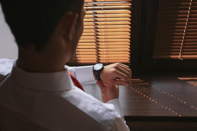 Vestiti dell'orologio dell'uomo d'affari, uomo d'affari che controlla il tempo sul suo orologio da polso. lancetta da uomo con orologio, orologio da polso da uomo, onorari dello sposo, preparazione del matrimonio, preparazione al lavoro, stile dell'uomo