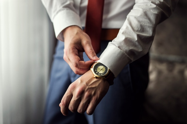 Vestiti dell'orologio dell'uomo d'affari, uomo d'affari che controlla tempo sul suo orologio. mano da uomo con orologio, orologio da uomo, spese dello sposo, preparazione del matrimonio, preparazione al lavoro