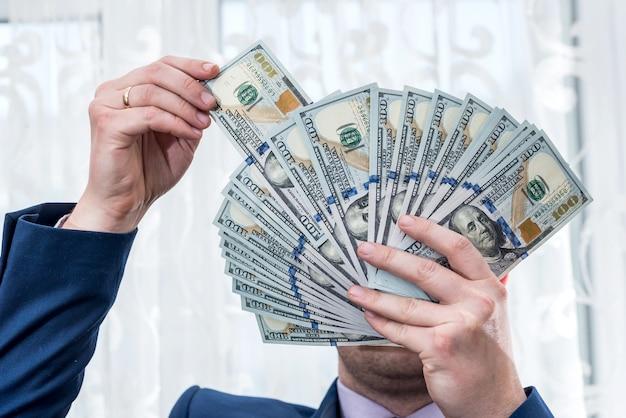 L'uomo d'affari ha chiuso la sua faccia con la ventola del dollaro