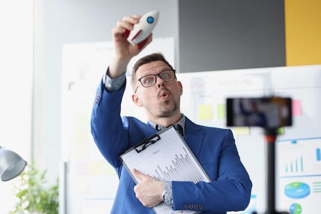 L'allenatore dell'uomo d'affari lancia un razzo e registra video di formazione sulla telecamera aprendo un piccolo e