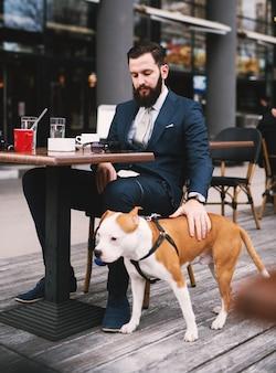 Uomo d'affari presso la caffetteria con il cane. migliori amici al bar.