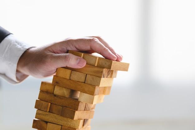 Uomo d'affari che crolla il blocco di legno impilato della torre a mano come fallimento o progetto in fallimento.