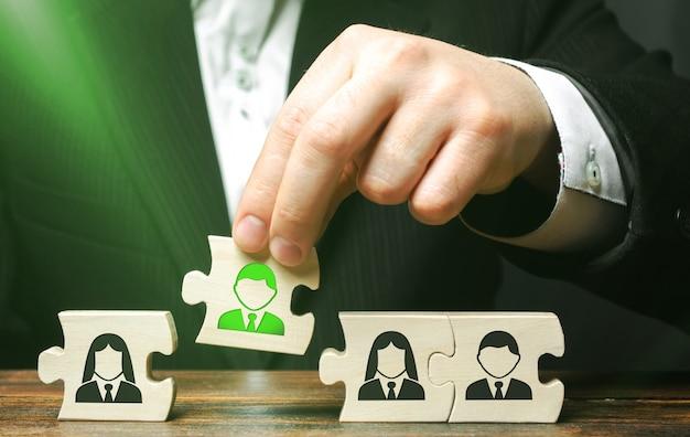 Un uomo d'affari raccoglie enigmi che simboleggiano il concetto di un team di dipendenti di creare un team aziendale