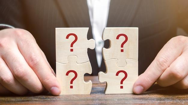 L'uomo d'affari raccoglie i puzzle con i punti interrogativi.