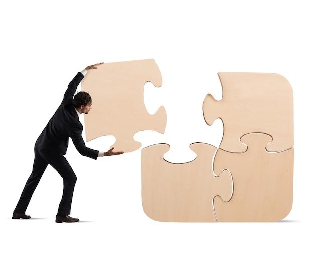 L'uomo d'affari completa un grande puzzle inserendo un pezzo mancante