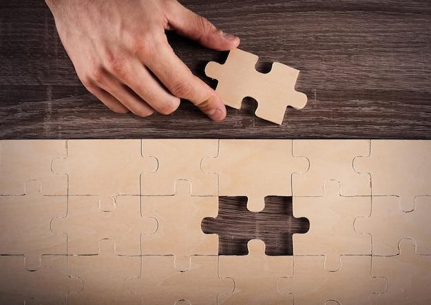 L'uomo d'affari completa un puzzle inserendo l'ultimo pezzo
