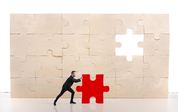 L'uomo d'affari completa un puzzle inserendo un pezzo rosso mancante