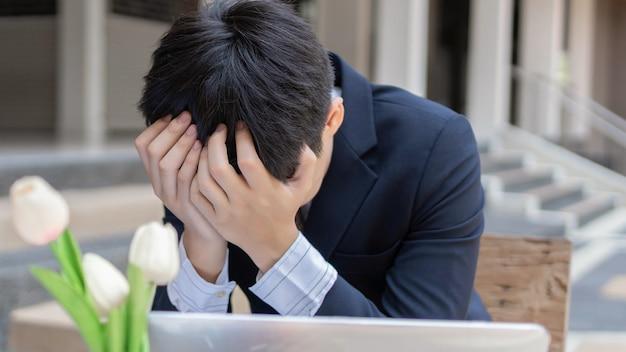 Concetto di uomo d'affari gli uomini d'affari che usano entrambe le mani che coprono la fronte sentendosi disperati a causa dell'incontro con il problema più grande.