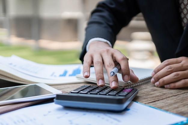 Concetto di uomo d'affari il ragioniere maschio che utilizza la calcolatrice per verificare la correttezza dei dati numerici nella tabella delle informazioni sul tavolo di legno.