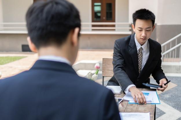 Concetto di uomo d'affari gli impiegati di sesso maschile che lavorano al compito di contabilità con la calcolatrice e il laptop all'interno dell'edificio.