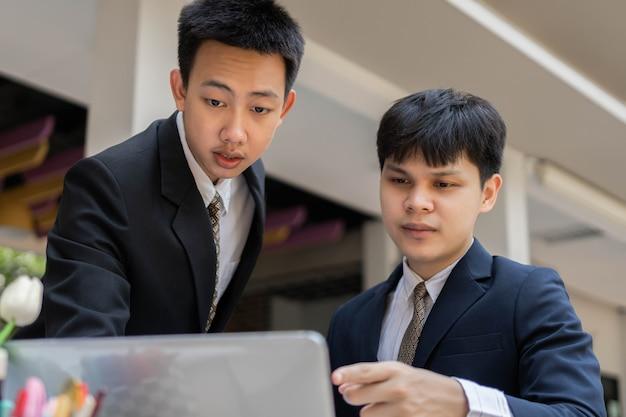 Concetto di uomo d'affari due uomini d'affari che indossano abiti ufficiali che si divertono a partecipare e a risolvere i problemi sul piano del progetto.