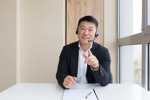 L'uomo d'affari conduce una consultazione online spiega con le mani usando un auricolare