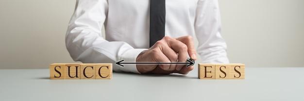 Uomo d'affari che collega due lati di blocchi di legno per scrivere la parola successo in un'immagine concettuale di potere e ambizione.