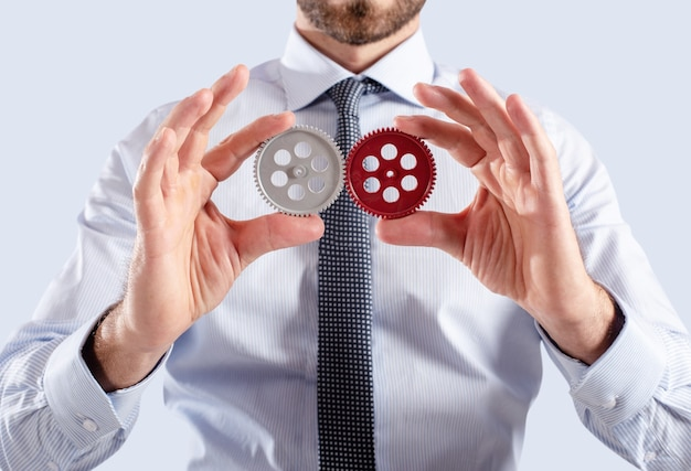 L'uomo d'affari collega il sistema di ingranaggi. il lavoro di squadra e il concetto di partenariato