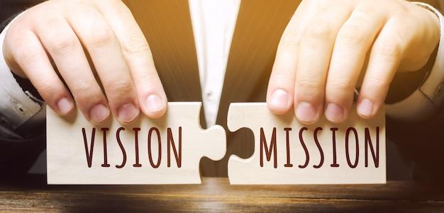 L'uomo d'affari collega i puzzle di legno con le parole vision mission. concetto per idee imprenditoriali
