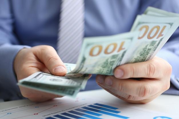 L'uomo d'affari considera dollari in contanti in ufficio