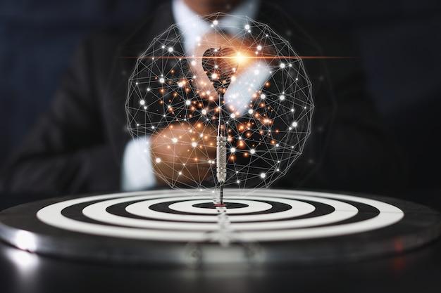 L'uomo d'affari che controlla il dardo ha messo sul bersaglio centrale la strategia e la tattica aziendale con un mondo grafico futuristico e un ologramma virtuale. idea per la competizione manageriale, il successo e la leadership.