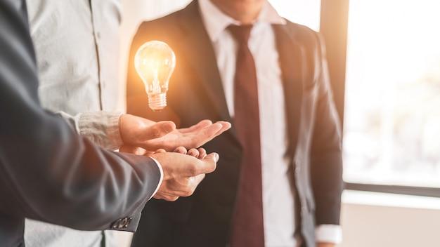 L'uomo d'affari controlla una lampadina che galleggia a mano, nuove idee con tecnologia e creatività innovative, lavoro difficile di concetto
