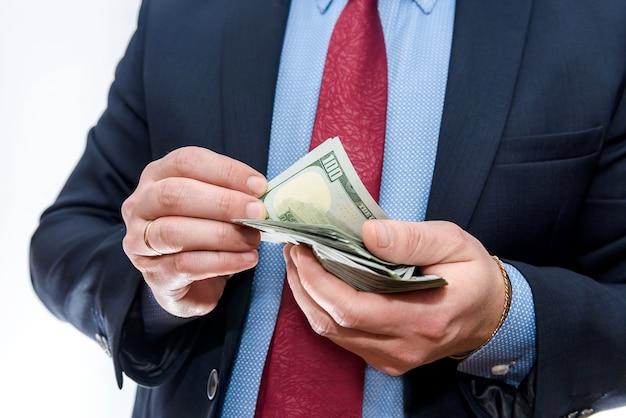 Uomo d'affari che conta le banconote del dollaro isolate su bianco
