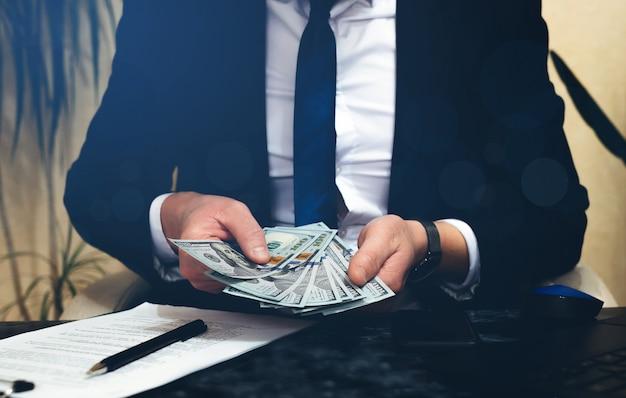 Imprenditore conteggio delle banconote in dollari sullo spazio di lavoro