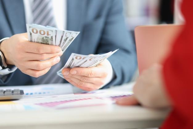 Uomo d'affari che conta le fatture del dollaro al primo piano della tabella. concetto di arricchimento illegale