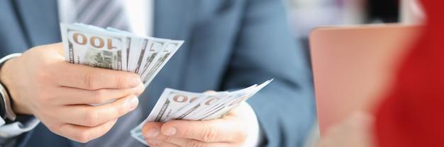 Uomo d'affari che conta le banconote in dollari al concetto di arricchimento illegale del primo piano della tavola