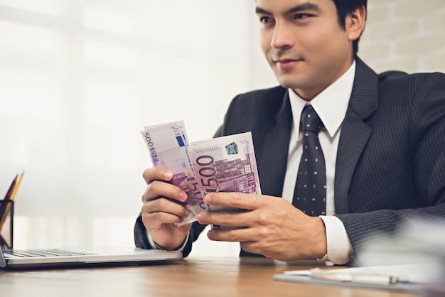 Uomo d'affari che conta soldi, banconote in euro, al suo scrittorio funzionante