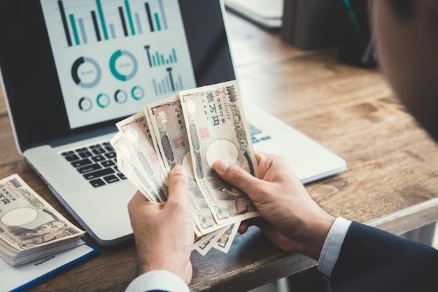 Uomo d'affari che conta soldi, banconote di yen giapponesi, davanti al computer portatile allo scrittorio funzionante