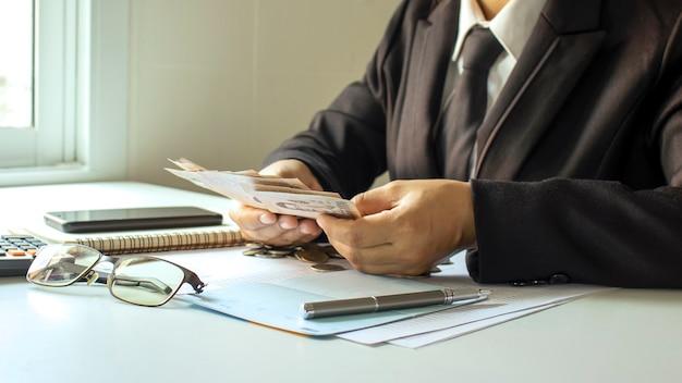 Uomo d'affari che conta soldi per verificare i conti aziendali