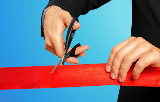 Uomo d'affari che taglia nastro rosso con le paia delle forbici