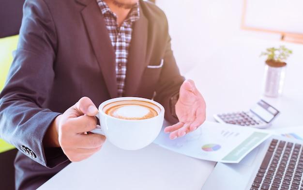 Uomo d'affari alla scrivania con una tazza di caffè
