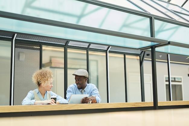 Uomo d'affari che discute un po 'di lavoro con la donna d'affari mentre beve il caffè che stanno all'edificio per uffici