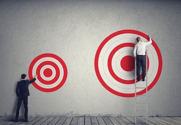 Uomo d'affari che disegna un obiettivo più grande del suo collega. raggiungere obiettivi più importanti nel concetto di lavoro
