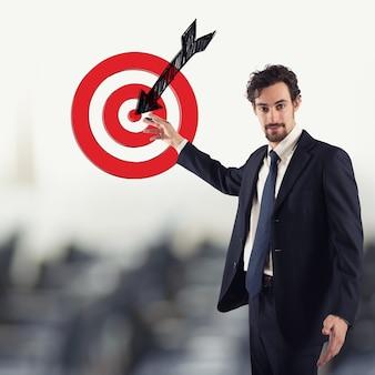 Uomo d'affari che disegna un bersaglio con la freccia. delinea il tuo concetto di obiettivi