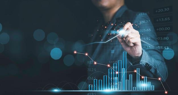 Uomo d'affari che disegna un grafico tecnico virtuale e un grafico per l'analisi del mercato azionario, gli investimenti tecnologici e il concetto di investimento di valore.