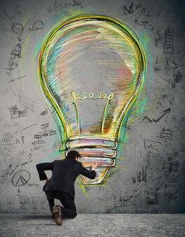 L'uomo d'affari disegna sul muro una grande lampadina colorata con colori vivaci e schizzi di affari