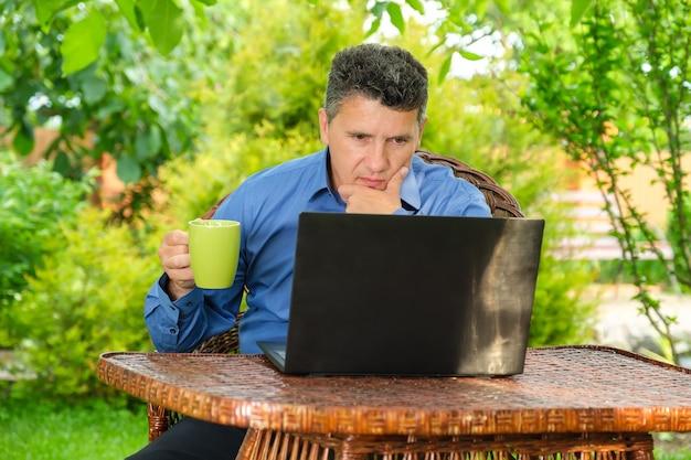 Uomo d'affari che beve caffè e legge notizie usando il portatile nel suo giardino