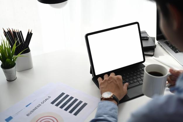 Uomo d'affari che beve caffè e lavora su tablet sulla scrivania in ufficio.