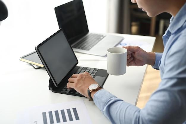 Uomo d'affari che beve caffè e lavora su tablet con diagramma di informazioni grafico alla scrivania in ufficio.