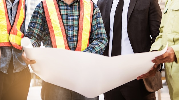 Riunione di ingegneria e uomo d'affari con architetto e guardando piano blueprint