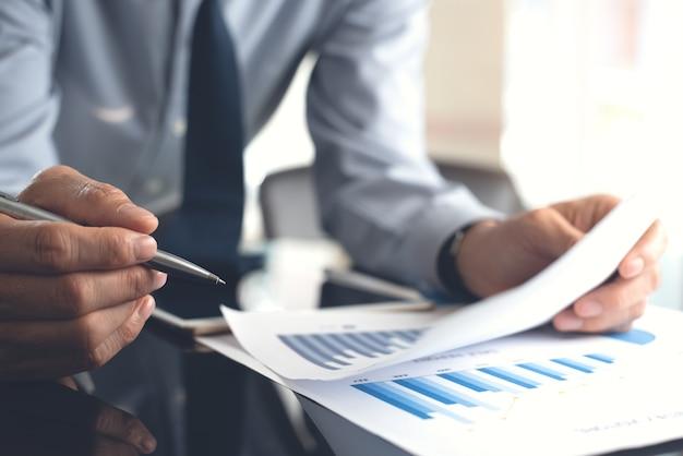 Uomo d'affari che esamina relazione aziendale sul tavolo in ufficio